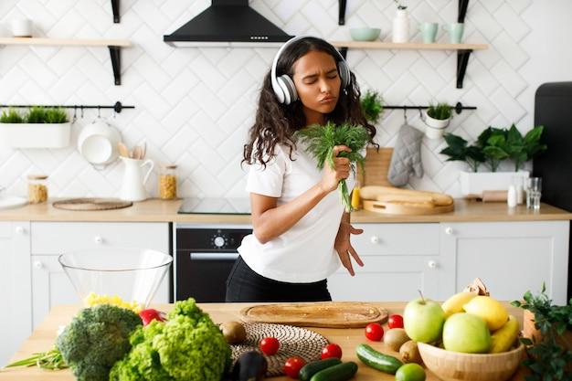 Esilarante donna mulatta con gli occhi chiusi in grandi cuffie sorride e finge emotivamente come se stesse cantando nel verde vicino al tavolo con frutta e verdura fresca