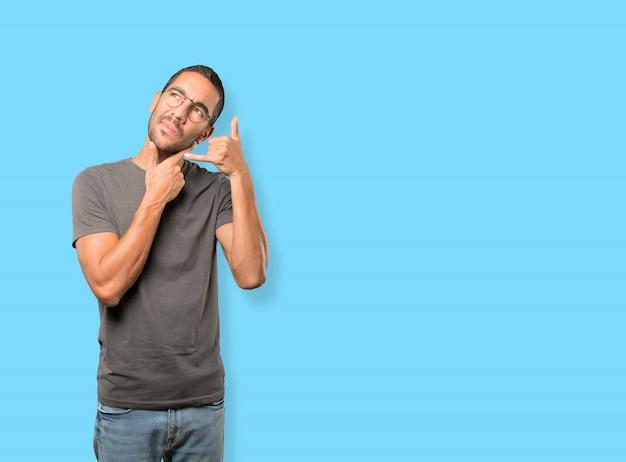 Esitante giovane che fa un gesto di chiamata con la mano