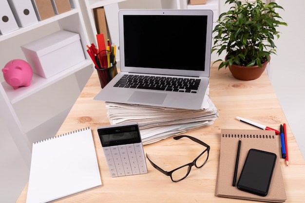 Esktop con laptop, occhiali, calcolatrice, penne, matite, carta, telefono e una pianta in ufficio