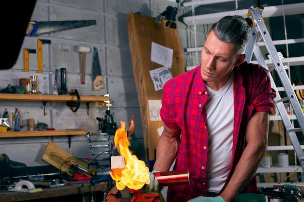 Esperto carpentiere che brucia una gamba di legno con un bruciatore a gas professionale. fiamme e fumo, fuoco e legname. ritratto di ebanisteria