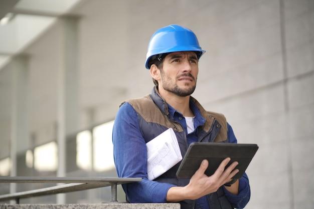 Esperto di costruzione bello in elmetto protettivo all'aperto con tablet e blueprint