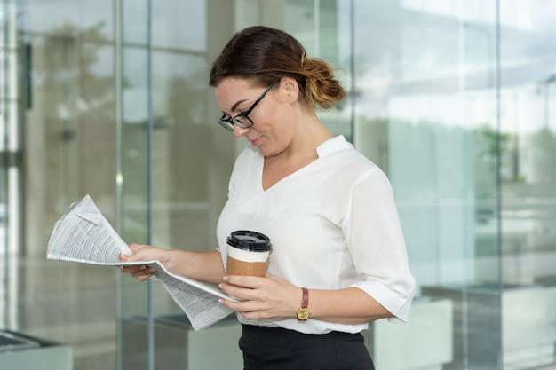 Esperto femminile concentrato che guarda attraverso le ultime notizie finanziarie