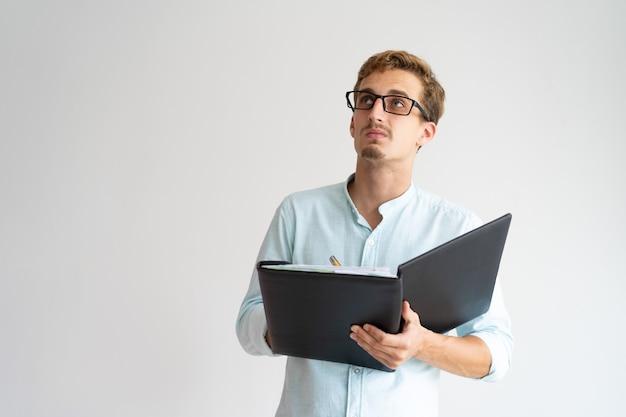 Esperto intelligente pensieroso guardando intorno e prendendo appunti.