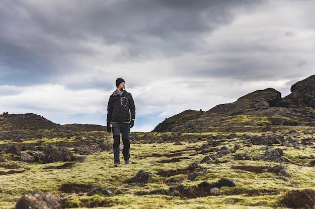 Esploratore che fa un'escursione in islanda sui campi di lava