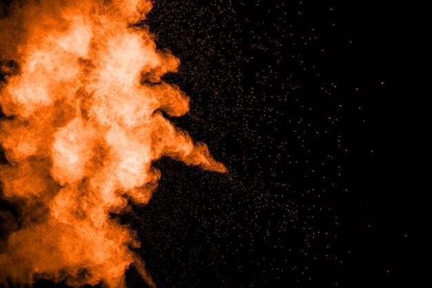 Esplosione astratta di polvere arancione su sfondo nero. movimento congelato di spruzzi di polvere d'arancia.