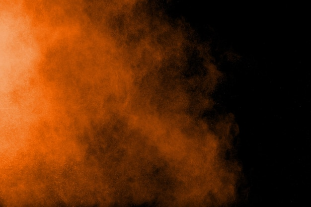 Esplosione astratta di polvere arancione su sfondo nero. spruzzi di particelle di polvere arancione.