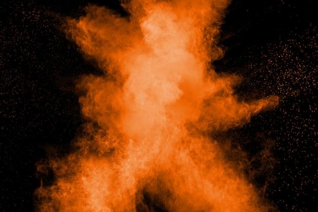 Esplosione astratta di polvere arancione su sfondo nero.