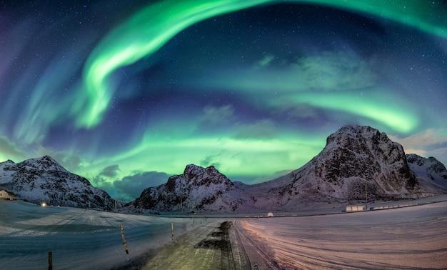 Esplosione di aurora boreale su catena montuosa innevata