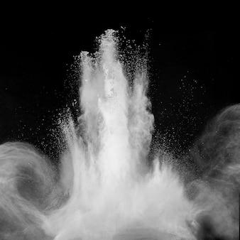 Esplosione di particelle di polvere bianca su sfondo nero.