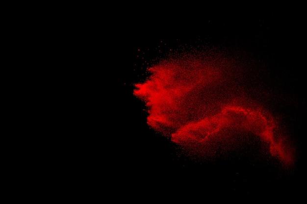 Esplosione di particelle rosse su sfondo nero. movimento congelato di spruzzi di polvere rossa