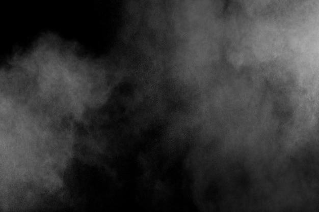 Esplosione di polvere bianca isolato su priorità bassa nera. spruzzata di particelle di polvere bianca.