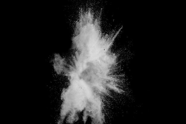 Esplosione di polvere bianca isolato su sfondo nero. spruzzi di particelle di polvere bianca