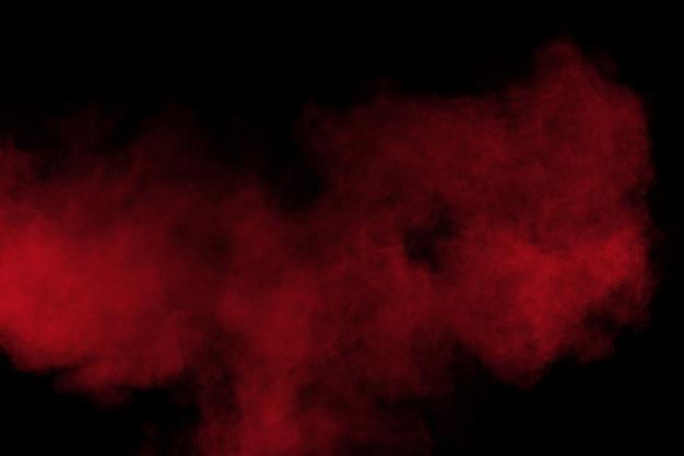 Esplosione di polvere di colore rosso su sfondo nero. movimento congelato di spruzzi di particelle di polvere rossa.
