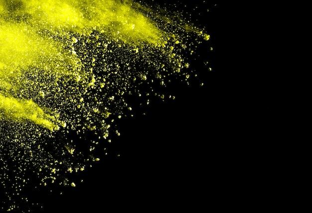 Esplosione di polvere gialla astratta su sfondo nero.