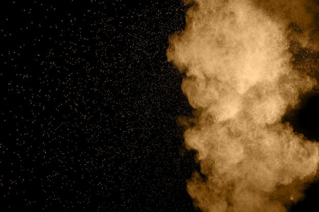 Esplosione di polvere marrone astratta su sfondo nero.