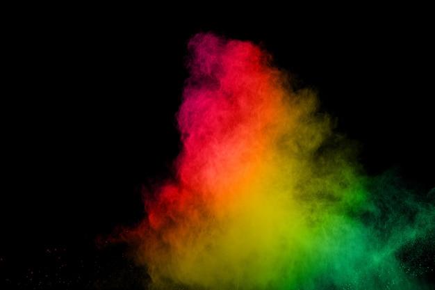 Esplosione di polvere multi colore astratto su sfondo nero. dipinto holi in festival.