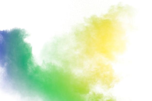Esplosione di polvere multicolore su fondo bianco particelle colorate lanciate su fondo.