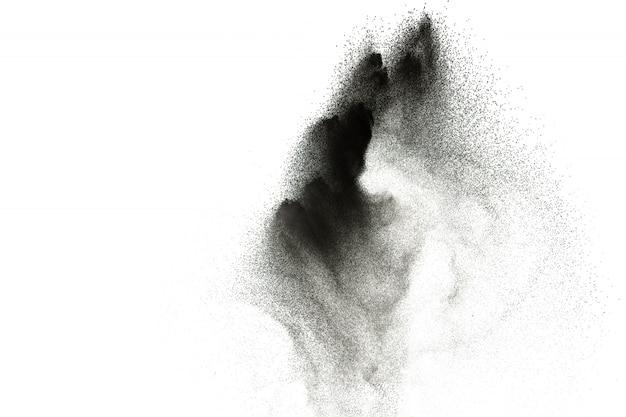 Esplosione di polvere nera su sfondo bianco. le particelle di polvere di carbone vegetale esalano nell'aria.