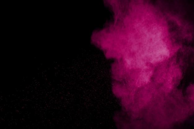 Esplosione di polvere rosa su sfondo nero.