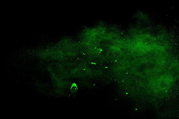 Esplosione di polvere verde su sfondo nero. spruzzata di particelle di polvere verde.