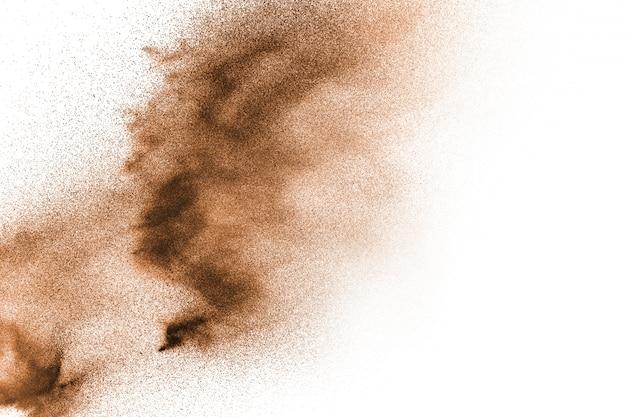 Esplosione di sabbia asciutta del fiume. spruzzata marrone della sabbia di colore contro bianco.