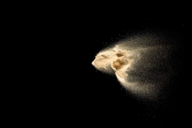 Esplosione di sabbia dorata isolato su sfondo nero