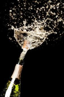 Esplosione di spruzzi di vino spumante champagne su fondo nero.