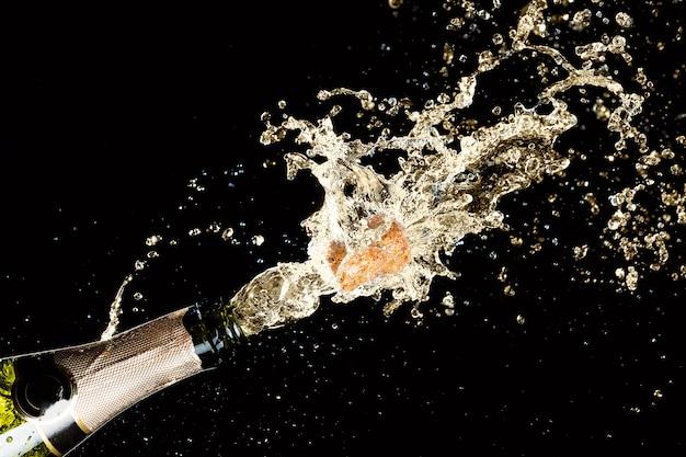 Esplosione di spruzzi di vino spumante champagne