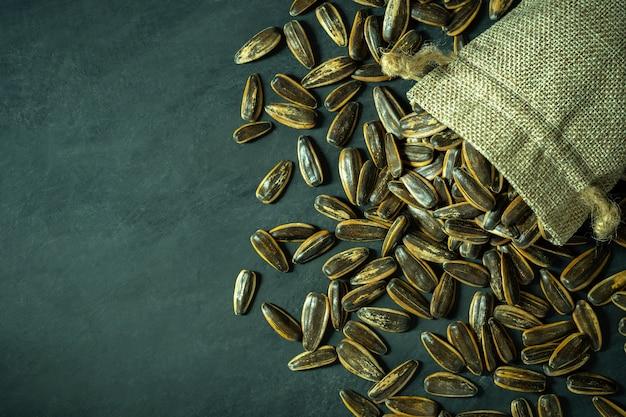 Esponga al sole i semi di fiore nella piccola borsa di tela da imballaggio sul pavimento nero del cemento