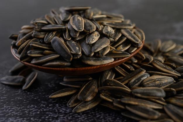 Esponga al sole il seme di fiore in una ciotola di legno sul pavimento nero del cemento.