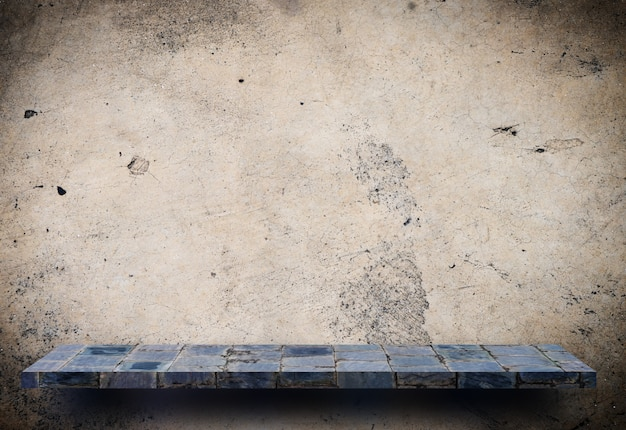 Espositore da banco in pietra grigia sul muro di cemento marrone