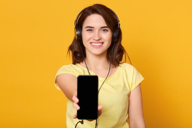 Esposizione di manifestazione della giovane donna del telefono cellulare mobile con lo schermo in bianco nero, femmina mora con i telefoni capi
