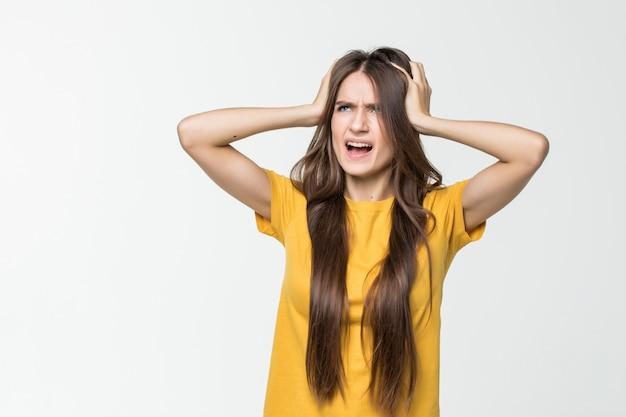 Espressione donna riccia emozione con le mani sulla testa su un muro bianco