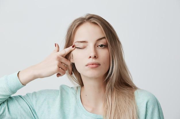 Espressioni del viso umano giovane bella donna premurosa con capelli lisci tinti di biondo in maglione a maniche lunghe azzurro che tocca con l'occhio di dito