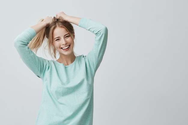 Espressioni ed emozioni del volto umano. la giovane bella femmina positiva con capelli lisci biondi tinti in coda di cavallo si è vestita in abbigliamento casual