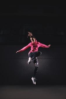 Espressionismo di una bella donna allegra che salta a mezz'aria in una stanza buia.