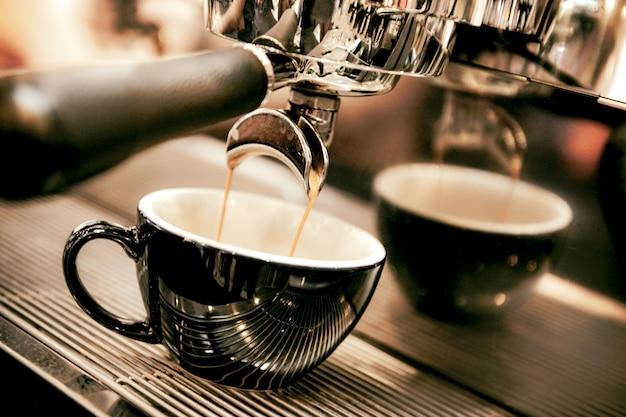 Espresso sparato dalla macchina per il caffè nella caffetteria