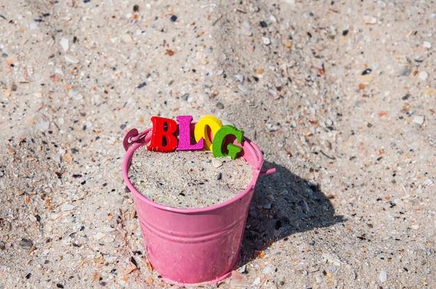 Esprima il blog delle lettere di superficie di legno in un secchio rosa con la sabbia