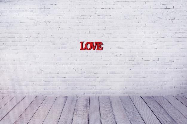Esprima l'amore dalle lettere di legno sulla parete del fondo bianco del mattone