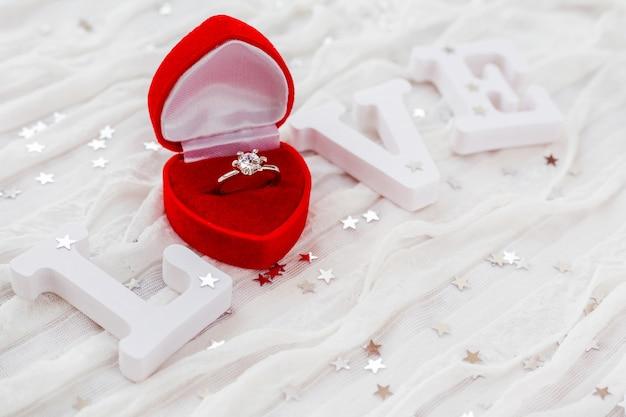 Esprima l'amore sul fondo bianco del tessuto con l'anello di diamante di fidanzamento in contenitore di regalo rosso.