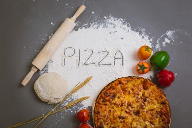 Esprima la pizza scritta su farina con una pizza saporita