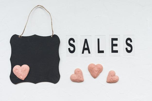 Esprima le vendite, il bordo nero ed i biscotti a forma di cuore su bianco