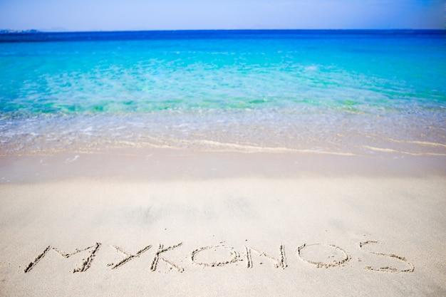 Esprima mykonos scritto a mano sulla spiaggia sabbiosa con l'onda di oceano morbida