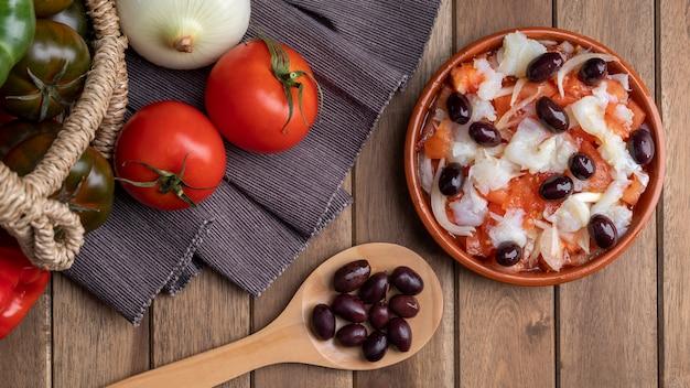 Esqueixada in vaso di terracotta e cucchiaio di legno con olive nere e pomodoro e cipolla. vista zenitale.