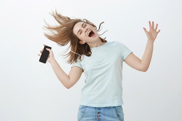 Essere selvaggio e libero mentre si ascolta una bella canzone. donna felice allegra che salta e balla con capelli castani mossi, occhi chiusi che canta lungo la musica d'ascolto della canzone preferita in cuffie che tengono smartphone