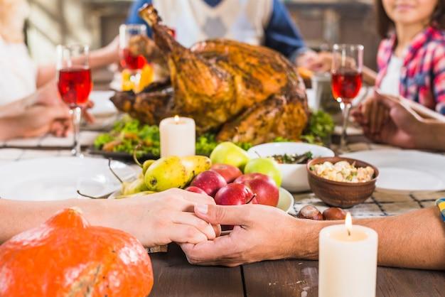 Essere umano che si tiene per mano al tavolo con il cibo