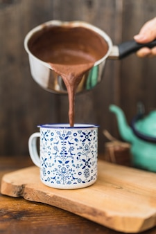 Essere umano con la padella della salsa che versa liquido marrone in tazza