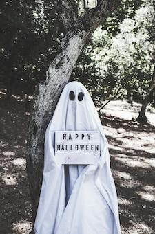 Essere umano in costume del fantasma vicino all'albero in foresta che tiene compressa di halloween