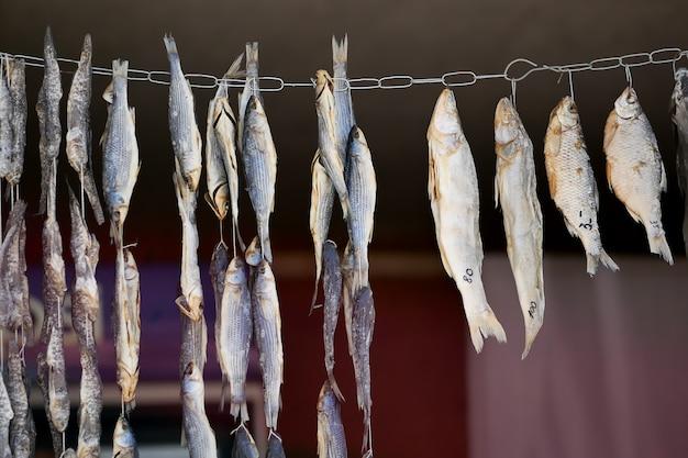 Essiccazione di piccoli pesci salati su una corda