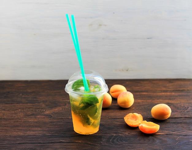 Estate bere limonata con arancia e menta nella tazza di plastica su uno sfondo scuro.